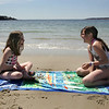 Gloucester: Isabel Locksmith, 10, and her friend Yona Kimball-Smith, 11, laugh after throwing sand at each other while enjoying the warm beach weather at Niles Beach Friday afternoon.  Mary Muckenhoupt/Gloucester Daily Times