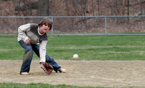 Rockport: Ryder Enos, 10, scoops up a ground ball while playing catch with his dad, David Enos, at Pingree Field yesterday afternoon. Despite the cold, Ryder likes to be barefoot. Photo by Kate Glass/Gloucester Daily Times Monday, April 20, 2009