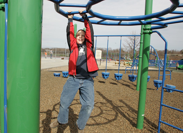 Rockport: Roland Curley, 7, of Gloucester goes across the monkey bars at the playground behind Rockport Elementary School Saturday afternoon.  Roland and his brother Frank, 5, came to check out the new playground and enjoy the spring weather. Mary Muckenhoupt/Gloucester Daily Times