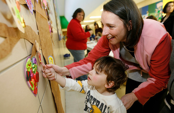 "Gloucester: Brandi Bonds helps her son, Quade, 2, place a star on his tree decoration during the O'Maley School's ""Vanilla, Strawberry, Picasso"" celebration of student work on Tuesday night. Over 400 people attended the event, which featured student projects, craft projects, and an ice cream social. Photo by Kate Glass/Gloucester Daily Times Wednesday, April 14, 2009"