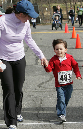 Manchester: Jenni Athanas runs with her son Sam, 3, as they cross the finish line of the Hit the Street for Little Feet Road Race at Manchester Memorial Elemenary School Saturday morning. The race was only one mile and began and ended at the school. Mary Muckenhoupt/Gloucester Daily Times