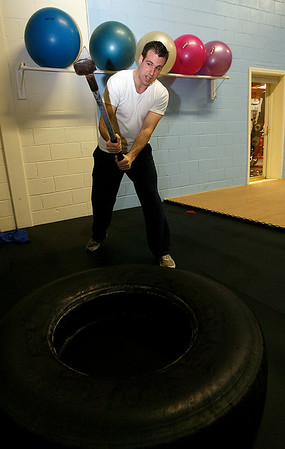 Gloucester: Aldo of Aldo's Fitness, demonstrates sledging, which works the core muscles. Aldo's Fitness offers a variety of group classes through Fitness Zone. Photo by Kate Glass/Gloucester Daily Times Monday, April 6, 2009