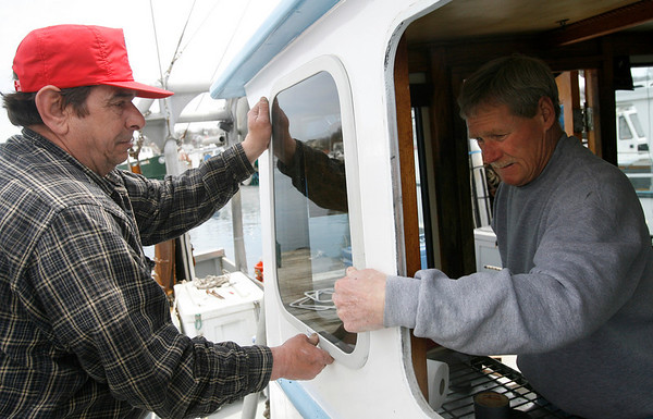 Gloucester: Busty Brancaleone, left, helps Sean Antrim install new windows on his boat, the Tina & Tom, at the Jodrey State Fish Pier on Wednesday afternoon. Busty says he's been forced to spend money on repairs during the two-month closure instead of being out at sea working. Photo by Kate Glass/Gloucester Daily Times Wednesday, April 22, 2009