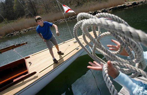 Gloucester: Tyler King, 12, throws a rope to his sister, Sara King, 9, as they help launch The Spirit, a 1940s Alden class sailboat, at River Boat Works at Montgomery Boat Yard yesterday afternoon. Photo by Kate Glass/Gloucester Daily Times Monday, April 27, 2009