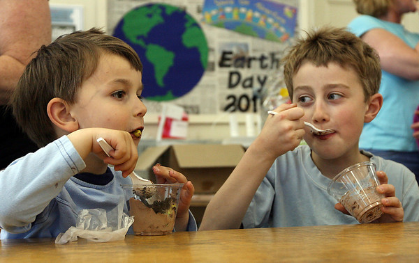 """Essex: Evan Fitzgerald, right, watches as his brother, Connor Fitzgerald, slurps down a gummy worm while eating chocolate """"dirt"""" at the TOHP Burnham Library on Thursday during an Earth Day celebration. Photo by Kate Glass/Gloucester Daily Times"""