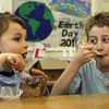 "Essex: Evan Fitzgerald, right, watches as his brother, Connor Fitzgerald, slurps down a gummy worm while eating chocolate ""dirt"" at the TOHP Burnham Library on Thursday during an Earth Day celebration. Photo by Kate Glass/Gloucester Daily Times"