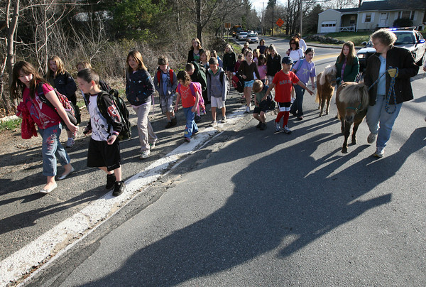 "Essex: Ellen Attridge and her daughter, Veronica, guide their miniature horses, Faith and Hope, alongside the ""walking school bus"" to Essex Elementary School yesterday morning. Photo by Kate Glass/Gloucester Daily Times"