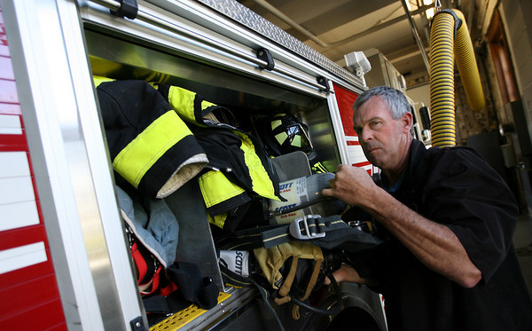 Rockport: Rockport Fire Chief Jim Doyle pulls an air tank from the ladder truck at central station. The department recently received $38,000 in federal money to replace their cascade system, which fills the air tanks. Photo by Kate Glass/Gloucester Daily Times