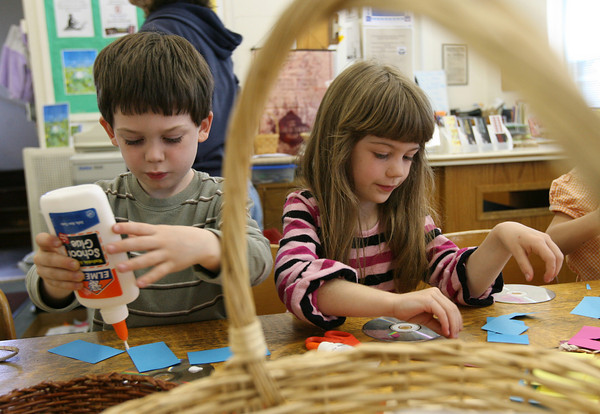 Essex: Kevin Adams, 4, and his sister, Heather Adams, 7, make crafts from recycled CDs during the TOHP Burnham Library's Earth Day celebration on Thursday. Photo by Kate Glass/Gloucester Daily Times