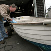 Essex: Ted Guldemond repairs a friend's fiberglass boat outside his Conomo Point garage yesterday afternoon. The boat had been damaged in one of the spring storms. Photo by Kate Glass/Gloucester Daily Times