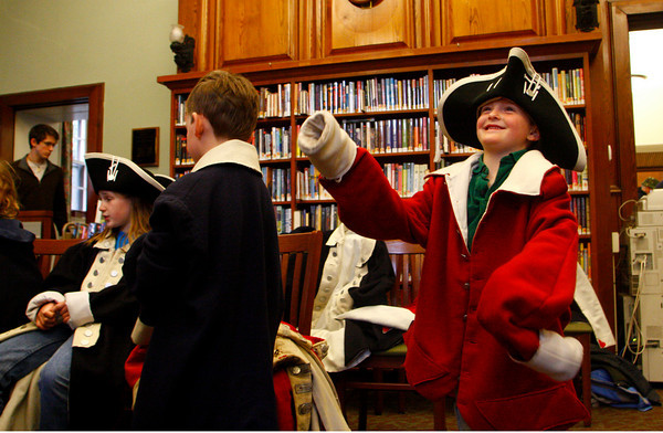 Manchester: Aidan Cunningham, 6, tries to move his arms as he tries on a coat from the Revolutionary War time period at the Manchester Public Library Saturday morning.  The Library held Revolutionary War Day and re-eneactment member Denis Cormier came with clothing to show kids what different soldiers form different parts America or the Bristiah and French would wear to battle. Also pictured is Aidan's brother, Connor, 6, and sister Caileigh, 10, left.  Mary Muckenhoupt/Gloucester Daily Times