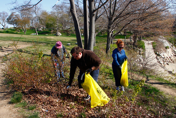 Gloucester: Patrick Kenney picks up trash at Satge Fort Park with his mother Maureen, left, and sister Priscilla Saturday morning. Patti Amaral of the Clean City Initiative organized the Earth Day cleanup at Stage Fort Park and also asked people to bring fresh fruits and vegetables to be donated to The Open Door Food Pantry. Mary Muckenhoupt/Gloucester Daily Times