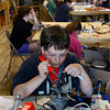 Gloucester: Rockport eighth grader David Kluge works on soldering the toggle switches that control the left and right movement of his submersible remote operated vehicle at the Maritime Heritage Center Thursday afternoon. 20 Rockport Middle School students have spent their vacation week at the Maritime Heritage Center building remotely operated underwater vehicles.  This program is a component of a 3-year NOAA grant the Heritage Center received that's directly focused on environmental education for Rockport students. Mary Muckenhoupt/Gloucester Daily Times