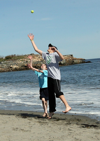 """Rockport: Drew Foley leaps above his sister, Molly Foley, to catch the ball while playing at Cape Hedge Beach on Monday. The two were playing """"Monkey in the Middle"""" with their brother, Quinton Foley (not shown). Photo by Kate Glass/Gloucester Daily Times"""
