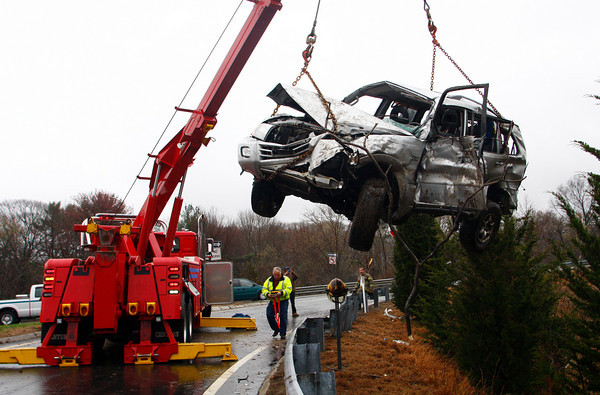 Gloucester: Tally's Towing Service lifts the suv that rolled off an embankment at exit 13 on Rt. 128 yesterday afternoon.  The woman involved was pinned under her car for over an hour before he Gloucester Fire Departement was able to free her. Mary Muckenhoupt/Gloucester Daily Times