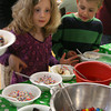 Essex: Riley Huber, 5, and Tyler Huber, 7, eye a variety of toppings for their ice cream during Essex Elementary School's Ice Cream Social during their annual Scholastic Book Fair on Tuesday night. The book sale ends today. Photo by Kate Glass/Gloucester Daily Times