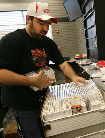 Gloucester: Corey Buffum of Gloucester, the manager of GameStop in Gloucester Crossing, organizes video games as the store prepares for its opening tomorrow. Photo by Kate Glass/Gloucester Daily Times