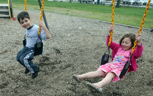 Manchester: Monet Vinciguerra watches as a few raindrops hit her legs as she swings with her brother, Max, at Masconomo Park on Tuesday afternoon. Photo by Kate Glass/Gloucester Daily Times