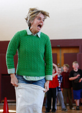 Rockport: Teacher Jen Dahlgren jumps in a potato sack race at the Kangaroo Hop staion of the Australian Olympics at the Rockport Elementary School Thursday afternoon.  The second graders took place in the olympics which included a Dingo Dash, Gum Tree Climbing and Ayer Rock Climbing. Mary Muckenhoupt/Gloucester Daily Times