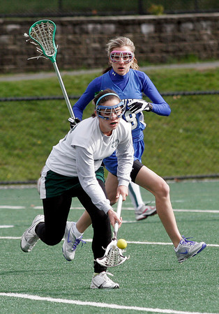 Manchester: Manchester Essex's Hillary Doucette scoops up the ball as Danvers' Anna Dinitto stays close by at Coach Ed Field Field yesterday afternoon. Photo by Kate Glass/Gloucester Daily Times