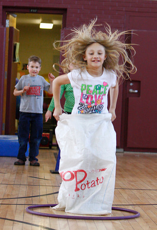 Rockport: Katie McInerney jumps in a potato sack race at the Kangaroo Hop staion of the Australian Olympics at the Rockport Elementary School Thursday afternoon.  The second graders took place in the olympics which included a Dingo Dash, Gum Tree Climbing and Ayer Rock Climbing. Mary Muckenhoupt/Gloucester Daily Times