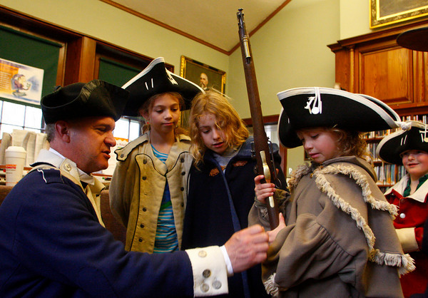 Manchester: Denis Cormier, a re-enactment member fo the Massachusetts 7th Regiment, lets Mia Cromwell, 7, hold a bayonette from the Revolutionary War period as Jade Cromwell, 9, and Emma Brophy, 9, look on at the Manchester Public Library Saturday morning.  The library presented Revolutionary War Day in honor of Patriots Day to help kids learn about what is was like to live in the 18th century and what war was like for soldiers at that time. Mary Muckenhoupt/Gloucester Daily Times