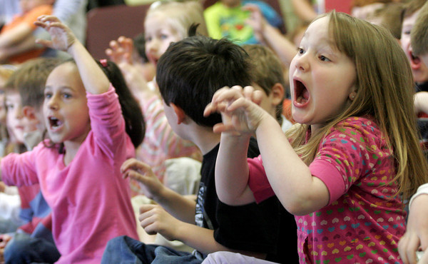 """Rockport: Eliza Smith, right, and Mya Doucette act like lions as a chamber group from Rockport Music performs """"Carnival of the Animals"""" by Camille Saint-Saens at Rockport Elementary School yesterday morning. Photo by Kate Glass/Gloucester Daily Times"""