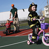 Gloucester: Julien Willey, 5, leads a bicycle procession including Emma Edgerton, 6, left, Kael Edgerton, 3, and Liam Edgerton, around the basketball court at the Fort on Thursday afternoon. Since Julian was dressed as a firefighter, Emma was pretending to be a police officer directing the procession. Photo by Kate Glass/Gloucester Daily Times