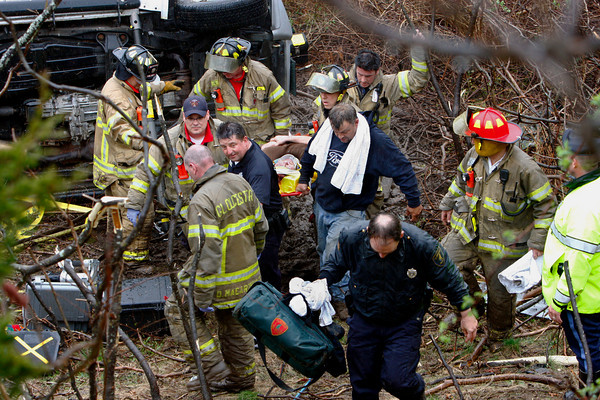Gloucester: Crews carry a women up an embankment after after her suv rolled off Rt. 128 Thursday afternoon. Crews works for over an hour to remove the women who was pinned under her car. Mary Muckenhoupt/Gloucester Daily Times