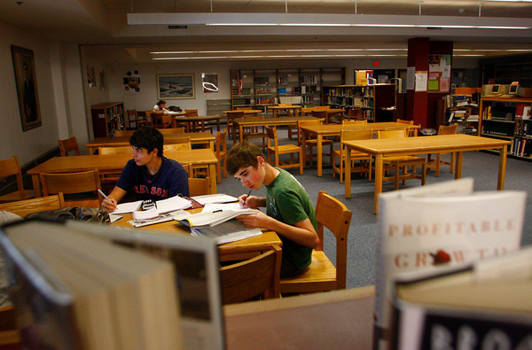 Gloucester: Marcus Cottone and Sean Gillion, right, get some school work done at the library at Gloucester High School Wednesday afternoon.  The New England Association of Schools and Colleges says the Gloucester High School Library is underutilized and that the rest of the building fails to reach fire, health and safety regulations. The organization is expected to sign off on Gloucester High School accreditation soon. Mary Muckenhoupt/Gloucester Daily Times