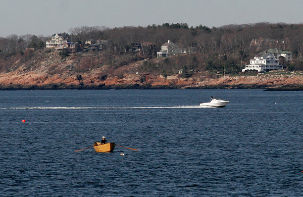 Gloucester: A man rows a dory boat just off Niles Beach yesterday morning as a motor boat heads into the harbor. Photo by Kate Glass/Gloucester Daily Times