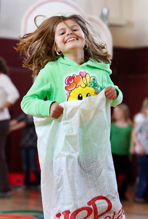 Rockport: Collen Murphy jumps in a potato sack race at the Kangaroo Hop station of the Australian Olympics at the Rockport Elementary School Thursday afternoon.  The second grade classes participated in the Austr;aian themed olympics which included a Dingo Dash, Gum Tree Climbing and Ayer Rock Climbing. Mary Muckenhoupt/Gloucester Daily Times