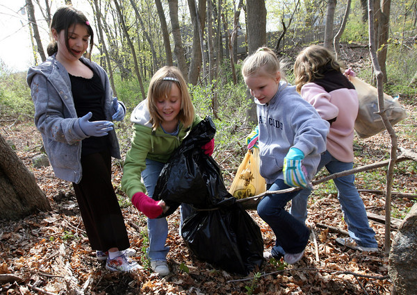 Gloucester: Alexia Thompson, Ruby Melvin, and Alexis Morris, all third grade students at West Parish Elementary School, pick up trash around the school's property yesterday morning. Members of the three third grade classes participating in the cleanup found a variety of items including underwear, tennis balls, cigarette butts, beer cans, and sciscors. Photo by Kate Glass/Gloucester Daily Times