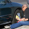 ALLEGRA BOVERMAN/Staff photo. Gloucester Daily Times. Gloucester: David Blake of Gloucester polishes the rims of his car along Stacy Boulevard on Monday afternoon. This rarely driven car used to belong to his uncle, and he restored it with a new paint job, removal of dents, addition of chrome accents, and takes careful care of it.