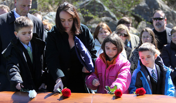 ALLEGRA BOVERMAN/Staff photo. Gloucester Daily Times. Gloucester: From left, Kyler, Leslie, Madeleine and Lucas McCaddon lay flowers on the casket of Capt. Michael Ryan McCaddon, M.D. at Calvary Cemetery on Tuesday afternoon after his funeral at St. Ann's Church.