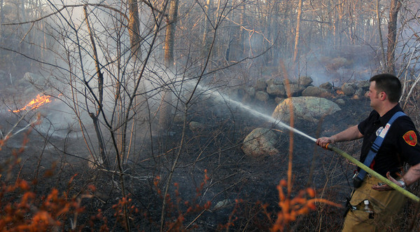 ALLEGRA BOVERMAN/Staff photo. Gloucester Daily Times. Gloucester: Rob Gerety of the Gloucester Fire Department attacks a piece of the leading edge of the brushfire in Dogtown on Thursday afternoon.