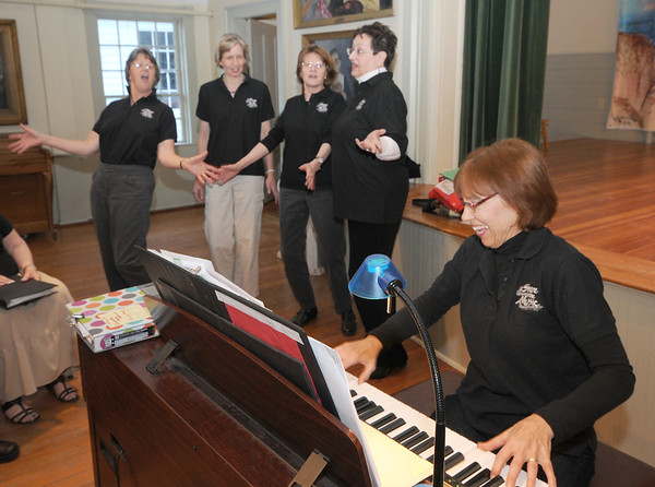 """Gloucester: Hiedi Dallin plays piano as from the left: Francis Fleming, Katzi Rueda, Kate Van Demark and Jackie Gravell sing """"My sister Kate"""" during  a""""Share the Music"""" rehearsal at Annisquam Town Hall. Jim Vaiknoras/staff photo"""