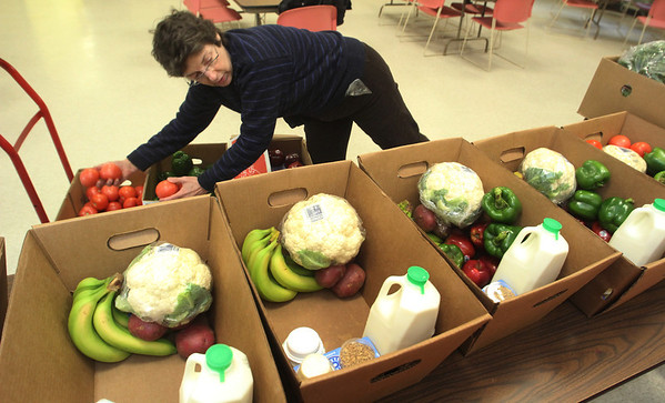 ALLEGRA BOVERMAN/Staff photo. Gloucester Daily Times. Gloucester: Every Wednesday, volunteer Carolin Catalano of Gloucester packs up special boxes for shut-ins at the Open Door for a pilot program called Good Food Box. It's a pilot program that started about a year ago in partnership with the North Shore Health Project. Each box is nutrition-specific and meant for people with specific health concerns. Soon it will be expanding to include people who have cancer and diabetes and target their special food needs. About 11 sets of two boxes each are put together - one full of perishable items and produce, the other with dry goods like cereal and then delivered each week.