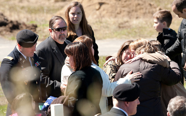 DESI SMITH/Gloucester Daily Times. Gloucester: Leslie McCaddon, second from lower left, speaks with her casualty affairs officer Capt. Jeffrey Clark, during the graveside service for her husband, Capt. Michael Ryan McCaddon on Tuesday at Calvary Cemetery.