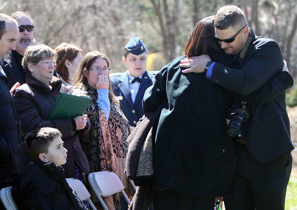 ALLEGRA BOVERMAN/Staff photo. Gloucester Daily Times. Gloucester: Family and friends of Capt. Michael Ryan McCaddon, M.D. at his graveside service with full military honors on Tuesday at Calvary Cemetery. Waya Schiller, right, a friend of his from the National Guard, hugs Leslie McCaddon. He did a reading during the funeral.
