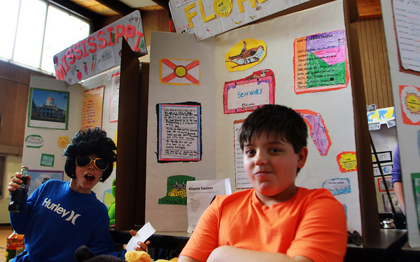 John Andrew, left, dresses as Elvis Presley, as part of his Mississippi display, and Cameran Smith dresses in bright colors, representing the sunshine state at the state fair at Plum cove Elementary School on Thursday afternoon. Jesse Poole/Gloucester Daily Times April 12, 2012