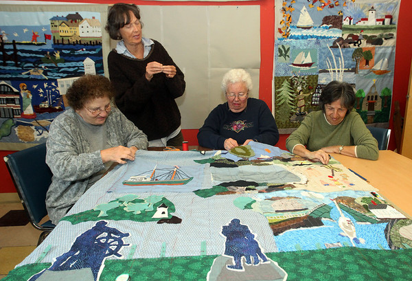 ALLEGRA BOVERMAN/Staff photo. Gloucester Daily Times. Gloucester: Seniors at the Rose Baker Senior Center in  Gloucester are designing and working to sew 18 quilts depicting each neighborhood in Gloucester. Each quilt depicts a different neighborhood with its distinctive iconic landmarks. Seven are in progress so far as a collaborative project to depict Gloucester as a community of neighborhoods. They would love people to help. Stop by the Rose Baker Senior Center between 10 a.m. and noon on Mondays, Tuesdays and Thursdays and go upstairs to the art room to participate. Working on a quilt depicting the Boulevard neighborhood on Monday morning are, from left: Ida Spinola, art director Juni Van Dyke, Judy Williams and Pauline Dion. Some other quilts in progress are on the wall behind them.