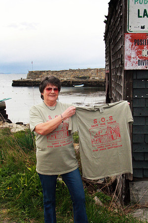 """Barbara Jobe of Lanesville sports a new T-shirt disigned to raise both finances and awareness for an effort to restore the historic Scandinavian shack at Lane's Cove. It depicts the shack itself and states above the image, """"S.O.S. Save Our Shack."""" These shirts are available for purchase at Woola on Washington Street in Lanesville. Jesse Poole/Gloucester Daily Times April 12, 2012"""