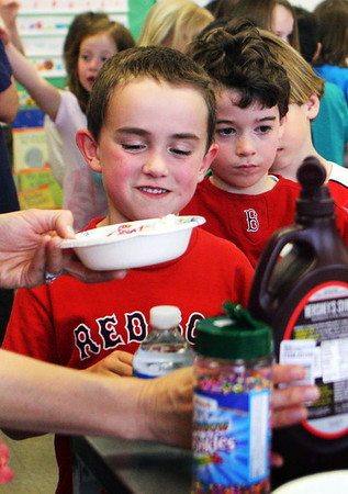 First-grader Elijah Walsh watches his ice cream carefully as it's about to be topped off with chocolate syrup at Essex Elementary School on friday afternoon. Jesse Poole/Gloucester Daily Times April 13, 2012