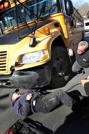 ALLEGRA BOVERMAN/Staff photo. Gloucester Daily Times. Gloucester: Mechanic John Wheeler, lying on the ground, of Gloucester Public Schools Transportation Department, pulls the school bus bumper back into place after it suffered an accident with a work truck on Tuesday afternoon as it was transporting children home from school at West Parish Elementary School. No one was injured, though the children on board were transported by a different bus to Addison Gilbert Hospital to be evaluated and released to their parents.