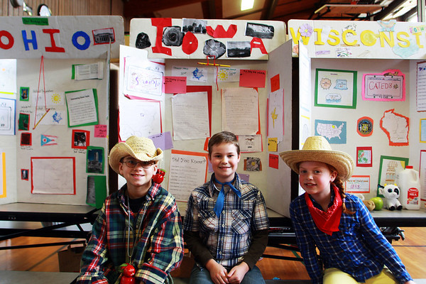 From left, Plum Cove Elementary School fourth-graders Cody Clifford, Adam Lane, and Cate Delaney sit in front of their state displays on Thursday afternoon, representing Ohio, Iowa, and Wisconsin for the school's state fair event. Jesse Poole/Gloucester Daily Times April 12, 2012