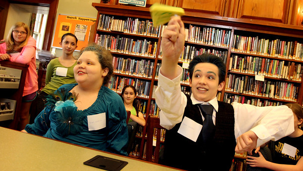 "ALLEGRA BOVERMAN/Staff photo. Gloucester Daily Times. Manchester: During a ""Hunger Games"" party at Manchester Public Library, Ben Willems, 14, right, on Team Peeta, is pitted against his sister, Sasa Willems, 10, of Team Katniss, in a game of Jeopardy based on the movie and book. There were various contests including trivia games, a jigsaw puzzle solving race, a costume/fashion display, cupcake decorating contest, archery contest, jellybean art and more during the event on Wednesday. Prizes were given throughout."