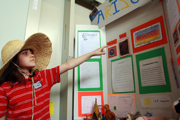 Annika Vanderberg, fourth grade, points to her drawing of the Arizona state license plate, one of her favorite things about her display of Arizona at the Plum Cove Elementary School state fair event o n Thursday afternoon. Jesse Poole/Gloucester Daily Times April 12, 2012