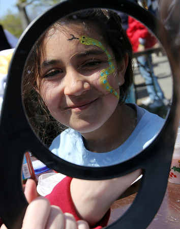 ALLEGRA BOVERMAN/Staff photo. Gloucester Daily Times. Gloucester: About 400 people walked in the 25th Annual Pride Stride through Gloucester on Sunday. At the community cookout following the fundraising walk, Sophia Hogan-Lopez, 10, of Gloucester, admires the snake painted on her face. She had a lady bug painted on the other side.
