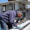 "ALLEGRA BOVERMAN/Staff photographer. Gloucester Daily Times. Gloucester: Ron Riley of Gloucester fixes the rail on his lobster boat, ""My Girls II"" on Monday morning in the city wharf at the 1-4, C-2 site."